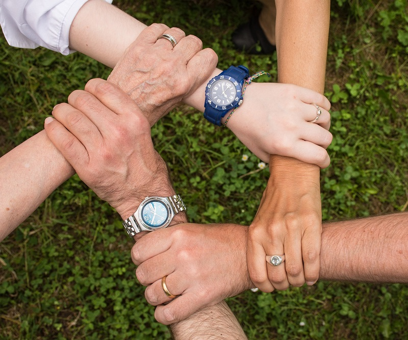 View from above of five left hands, each grasping the wrist of the hand to their left
