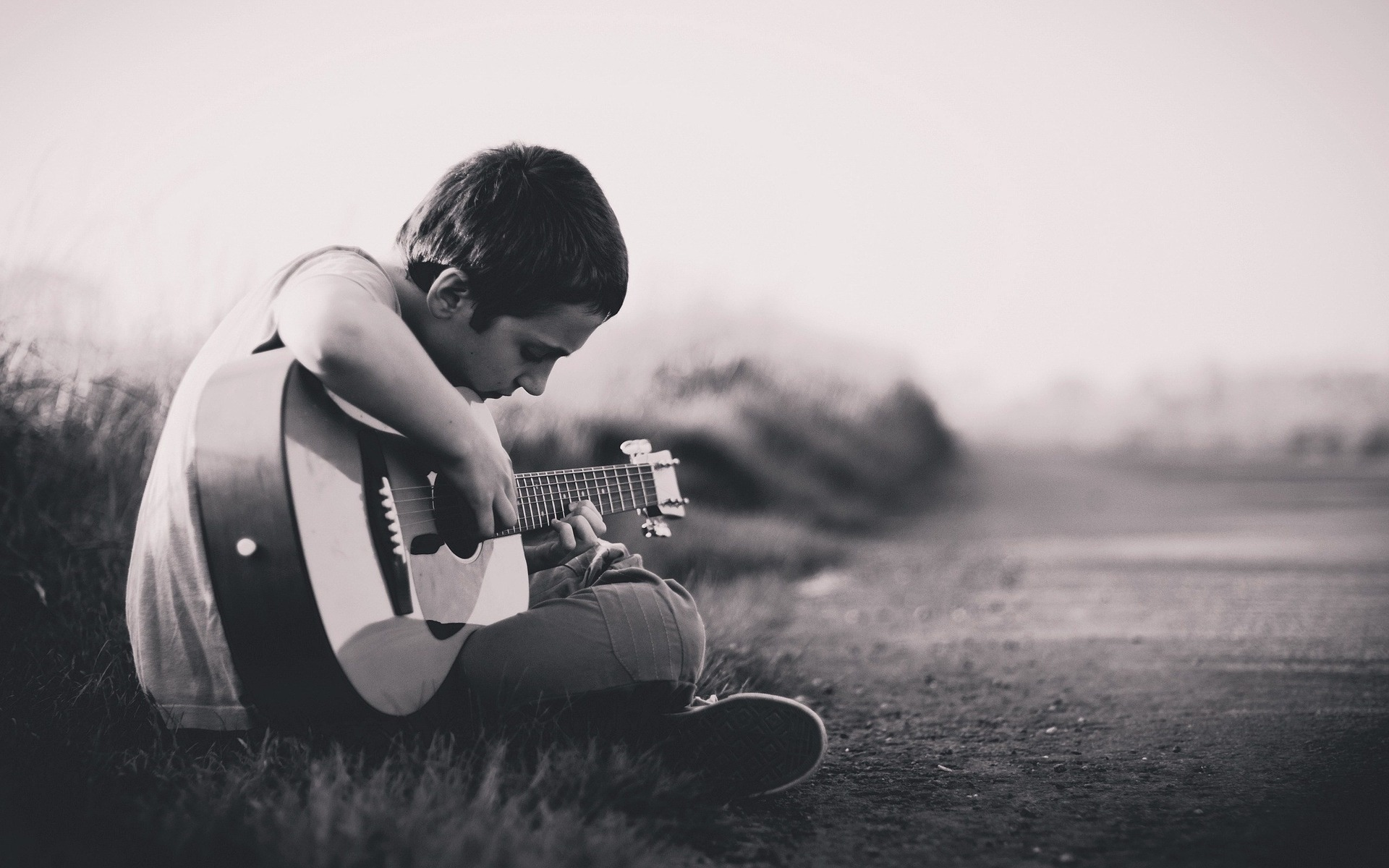 sepia-toned photo of boy playing guitar by side of rural road