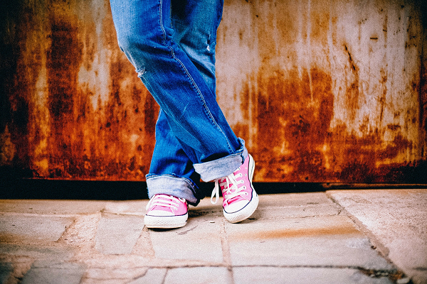 Young child's legs, wearing jeans and pink sneakers