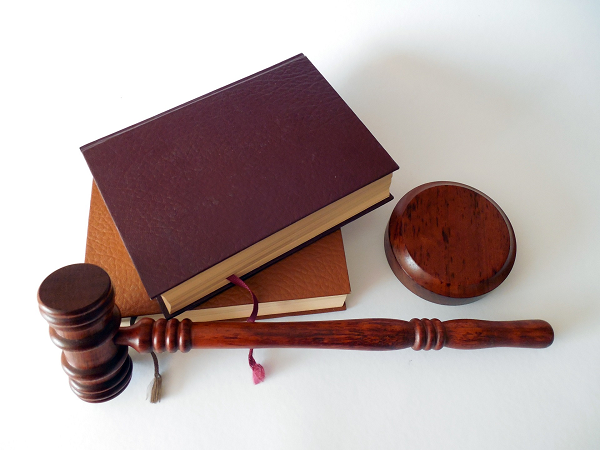 wooden gavel, two brown hardback books and a wooden block for gavel-tapping