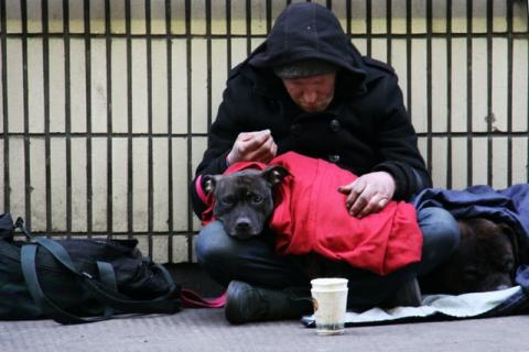 Picture of a homeless man sitting cross-legged on the ground curled over a dog in a red coat, on his lap. The dog is looking at the camera.